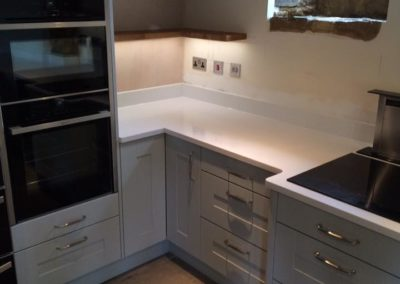 Partridge Grey kitchen, Silestone worktops, bespoke oak shelves, Neff slide & hide oven.
