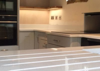 Silestone blanco maple with draining grooves, bespoke oak shelves with recessed LEDs, downdraft extractor